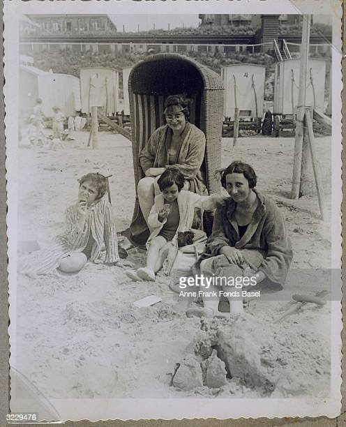 Margot Frank her sister Anne Frank and their mother Edith FrankHollander sitting on a beach in front of Mrs Schneider who is sitting in a wicker...