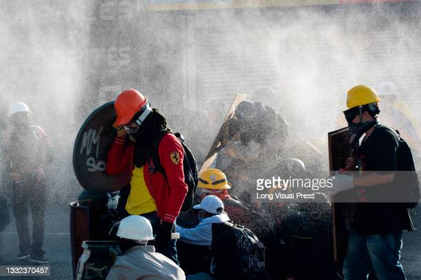 Front line demonstrators cover from water shot by a riot armored truck as demonstrations ended in late-night clashes between riot police and...