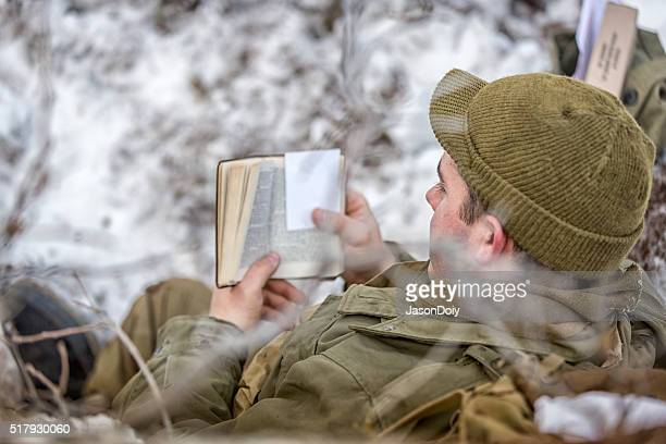 ww ii: front lines in the snow reading bible - soldier praying stock photos and pictures