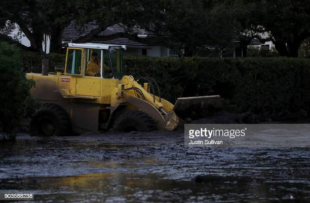 A front loader moves mud from a street following a mudslide on January 10 2018 in Montecito California 17 people have died and hundreds hundreds of...