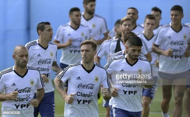 Argentina's midfielder Javier Mascherano midfielder Lucas Biglia and midfielder Ever Banega lead teammates while warmingup during a training session...