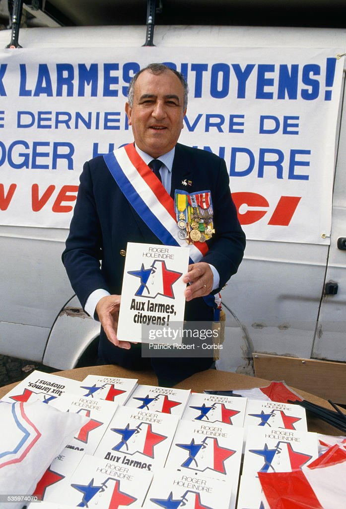 Front National vice president Roger Holeindre, head of the Department Protection Securite, sells books titled Aux larmes citoyens! or 'With the Tears Citizens!' at the Fete de Jeanne d'Arc, or Festival of Joan of Arc. Members of French right-wing political groups, including Front National leader Jean-Marie Le Pen, attended the annual festival.