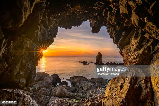 front of a cave entrance at sunset - light at the end of the tunnel stock pictures, royalty-free photos & images