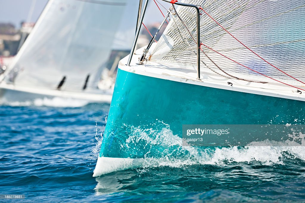 Front of a sailing boat in a regatta with waves hitting it : Stock Photo