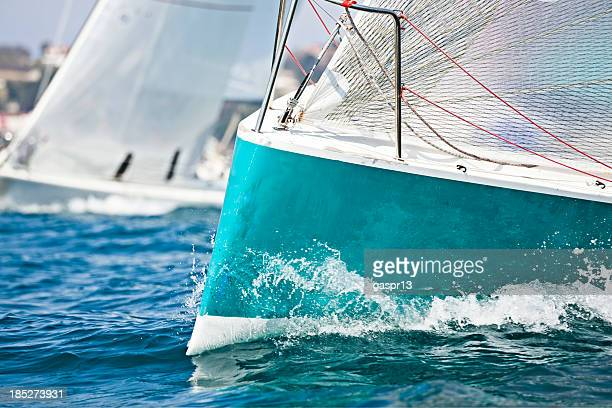 Front of a sailing boat in a regatta with waves hitting it