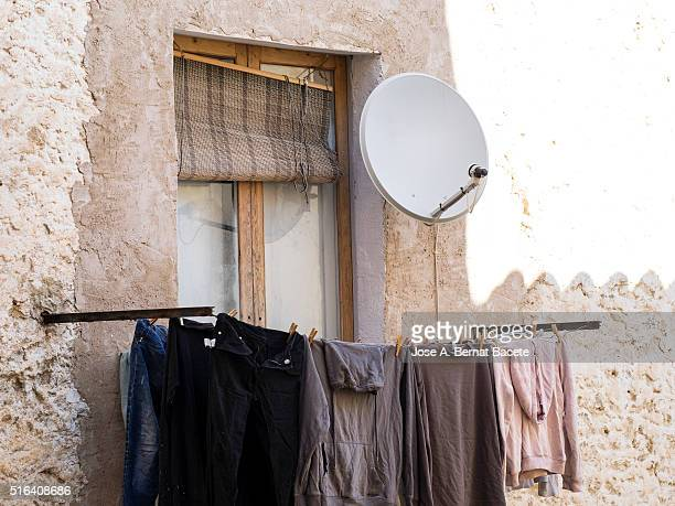 Front of an ancient house with the clothes stretched in the balcony and a satellite dish