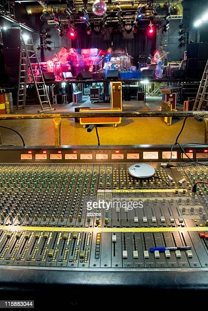 Front of house soundboard with band setting up on stage