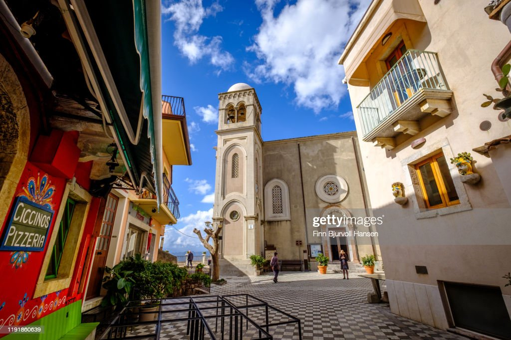 Castelmola, Taormina, Italy - November 8, 2019: Front of The Church of San Giorgio, pizzeria on the left side : Stock Photo