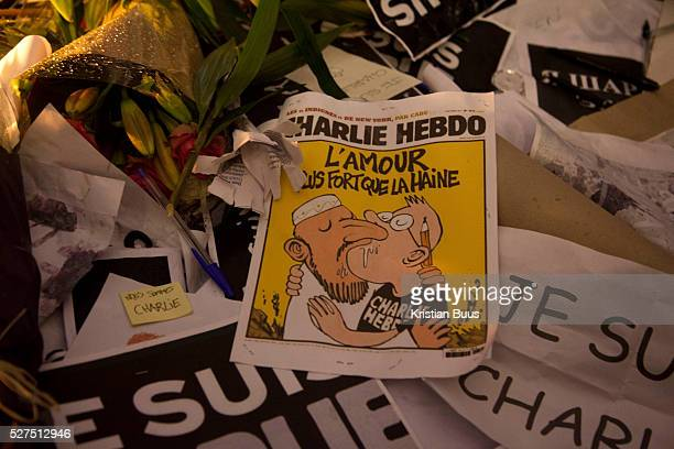 A front page from the Charlie Hebdo magazine states that love is stronger tha hate Londoners show their solidarity with the 12 people killed in an...