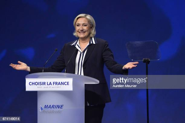 Front Party Leader and Presidential Candidate Marine Le Pen salutes the crowd as she arrives for a political meeting on April 27 2017 in Nice France...