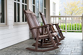 Front porch of house with brown rocking chairs and nobody in traditional american house