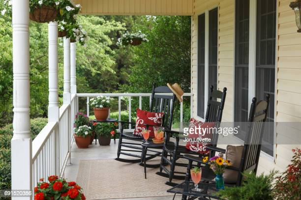 Front porch on home with hanging baskets and pink lemonade