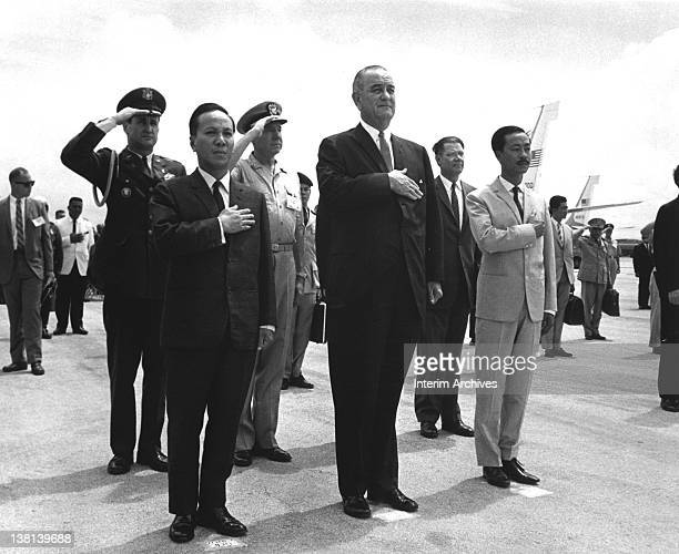 Front row, from left to right, Chairman Nguyen Van Thieu , President Lyndon B. Johnson and Prime Minister Nguyen Cao Ky salute during the playing of...