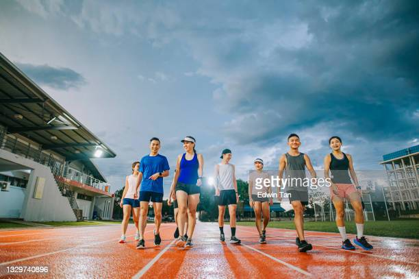 front view asian chinese sport team walking on track and field after the training at late evening with stormy cloud wet floor - forward athlete stock pictures, royalty-free photos & images