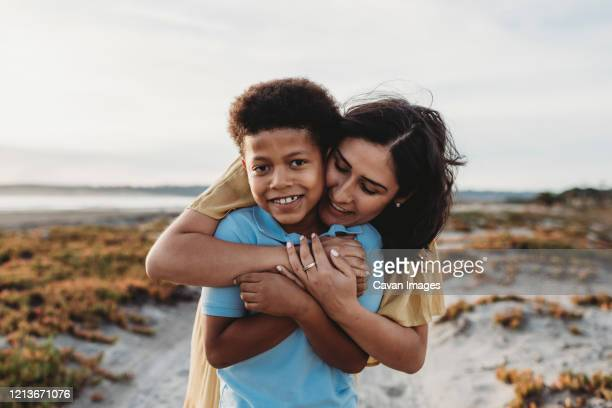 front view close up portrait of young mother embracing son beach - afro americano foto e immagini stock