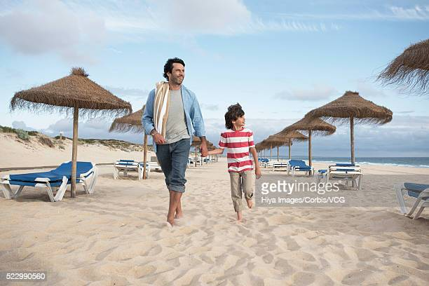 Front view father with son (10-12) walking on sandy beach