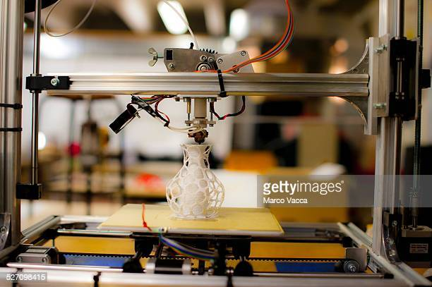 Front view of A 3d printer producing a model of a small vase