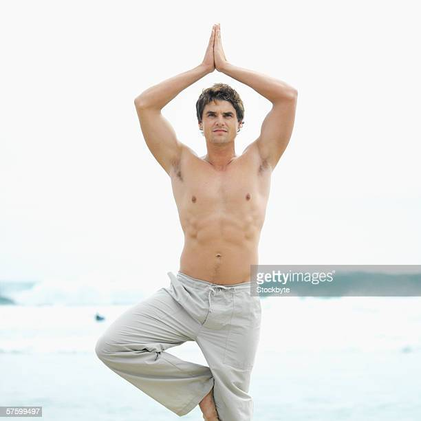 front view of a bare-chested man doing yoga at the beach - barechested bare chested ストックフォトと画像