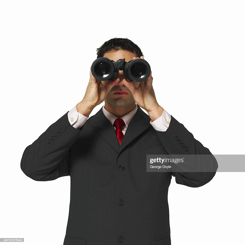 front view of a businessman looking through binoculars : Stock Photo