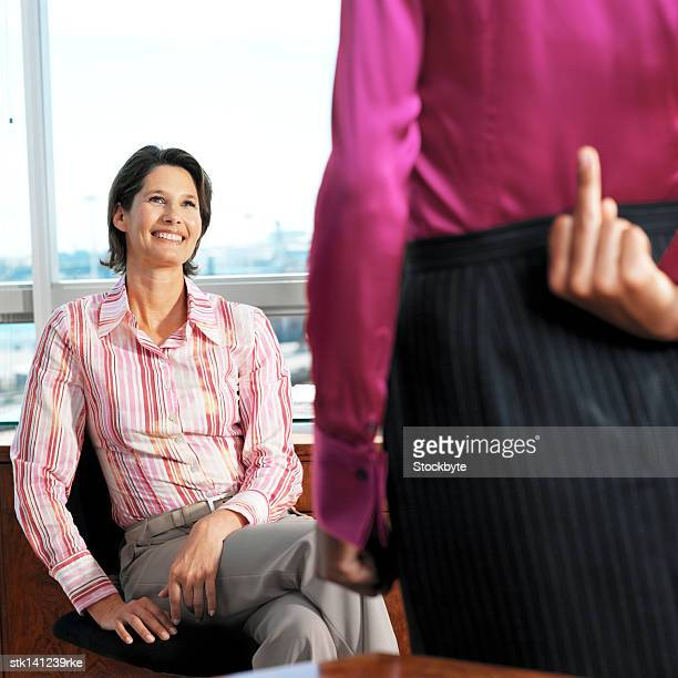 front view of a businesswoman and a rear view businesswoman standing putting her finger up behind her back