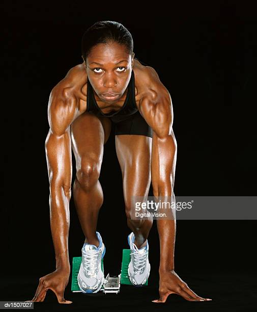 Front View of a Female Athlete Crouching in Starting Blocks