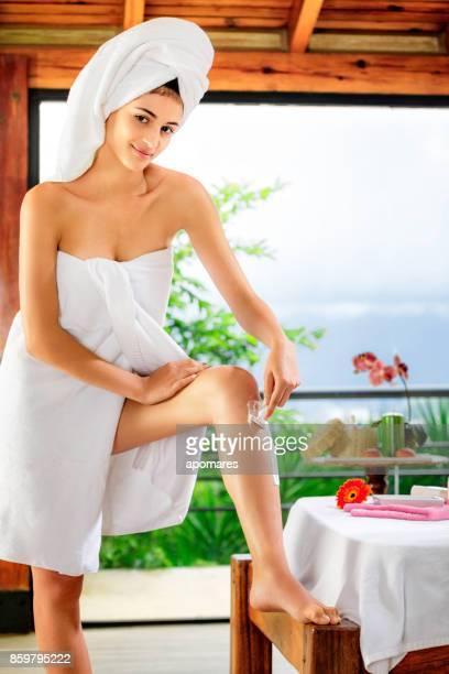 vista frontal de uma jovem hispânico permanente ao raspar as pernas após o banho - perna humana - fotografias e filmes do acervo