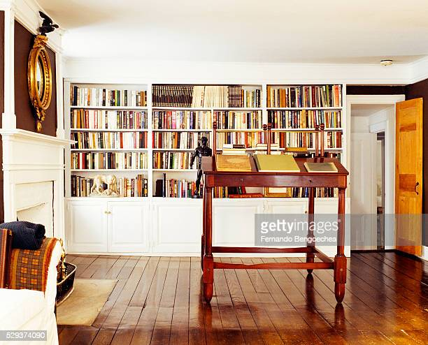 Front view of a large group of books arranged on bookshelves and an antique lectern