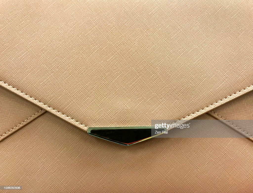 Front view of a light brown purse showing edge of flap and metal decor : Stock Photo