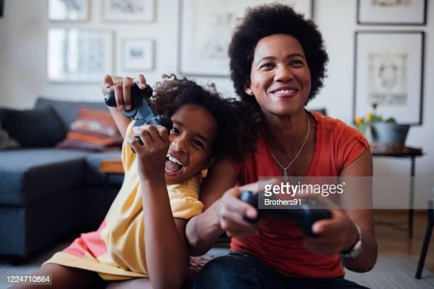 vista frontal de mãe e filha jogando videogame juntos - brincar - fotografias e filmes do acervo