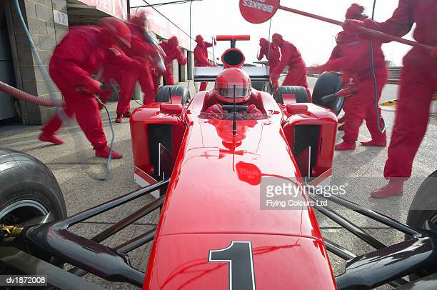 front view of a pit stop team working on a formula one racing car - coordinazione foto e immagini stock