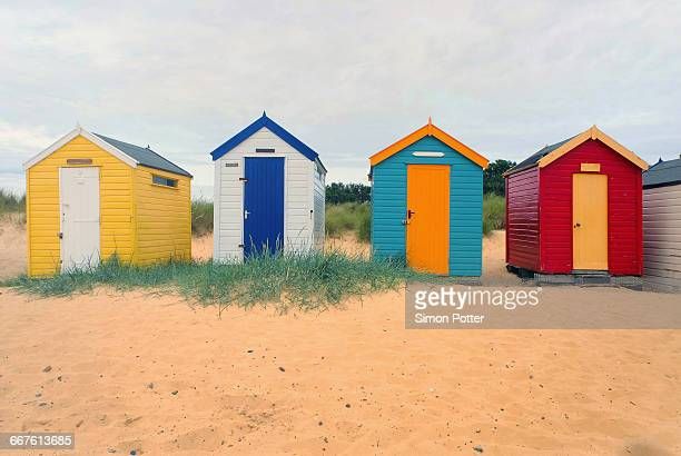 Front view of a row four multi-coloured beach huts, Southwold, Suffolk, United Kingdom