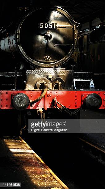 Front view of a vintage steam engine in the shadows of an engine shed at Didcot Railway Centre in Oxfordshire taken on August 19 2009