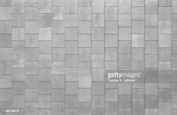 front view of a wall made of rusty square shaped tiles or slabs. high resolution full frame textured background in black and white. - タイル ストックフォトと画像