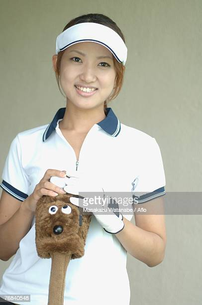 Front view of a woman holding a golf club with a cute cover