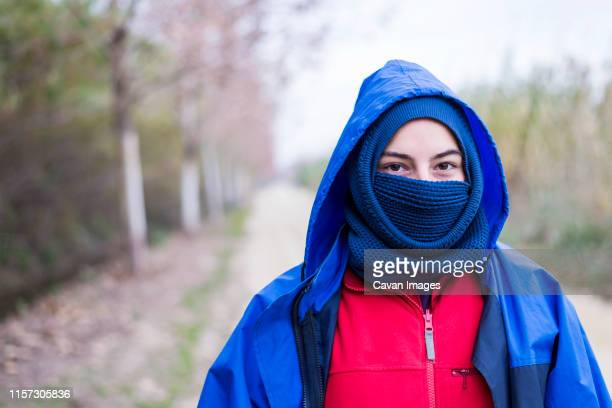 front view of a woman wearing a ski mask while standing outdoors and looking camera - balaclava stock pictures, royalty-free photos & images