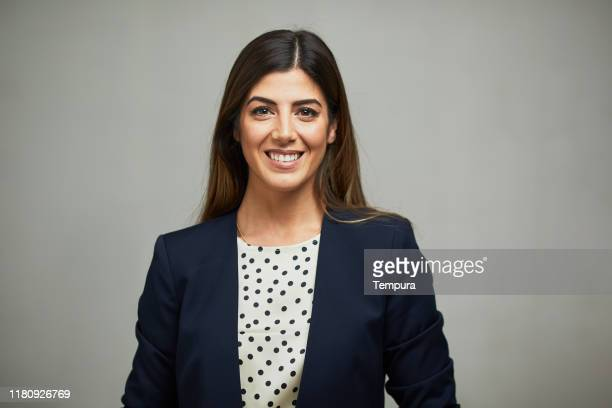 front view of a woman wearing a suit and smiling. - southern european descent stock pictures, royalty-free photos & images