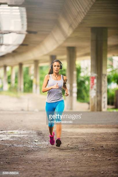 Front view of a young fit woman running.