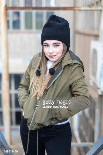 front view of a young teen standing outdoors with hands on pocke - three quarter length stock-fotos und bilder