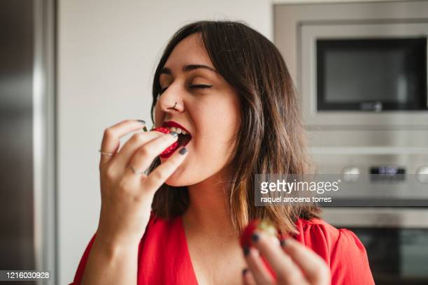 front view of a young woman in red shirt eating a strawberry in the home kitchen - red shirt stock pictures, royalty-free photos & images