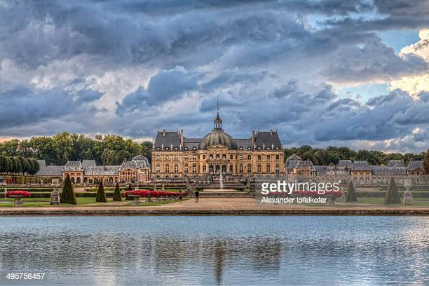 Front view of baroque Château de Vaux-le-Vicomte with pool in foreground and cloudy, dramatic sky, Maincy, France, April 2011.