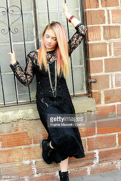 Front View Of Beautiful Fashion Model Standing Against Window On Brick Wall