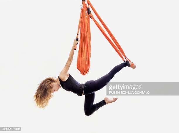 front view of blonde woman hanging on orange swing practicing aerial yoga. - artist stock-fotos und bilder