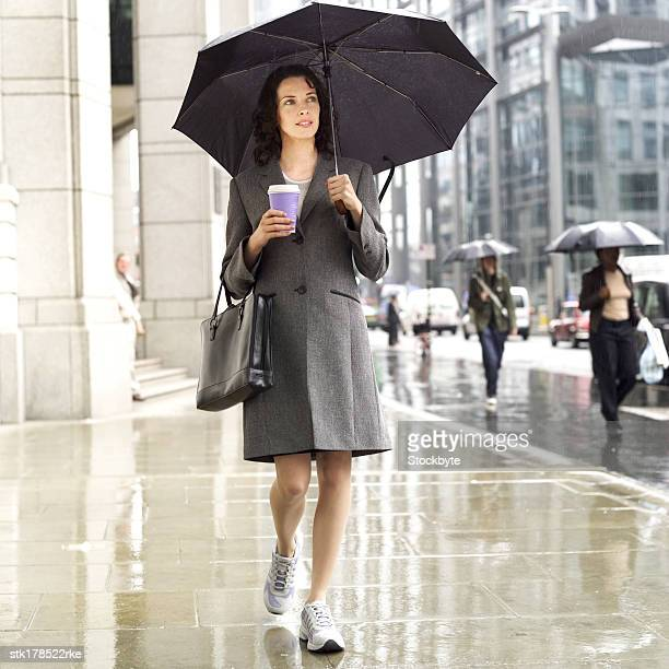 front view of businesswoman walking in the street in the rain holding umbrella and a takeaway coffee