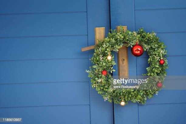 front view of christmas wreaths hanging on blue color door - wreath stock pictures, royalty-free photos & images