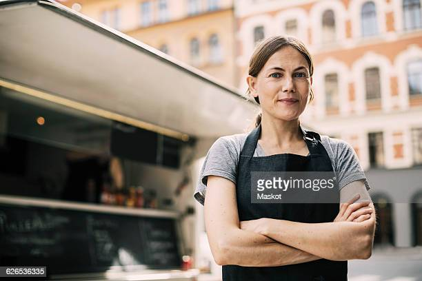 front view of confident female chef standing by food truck in city - schürze stock-fotos und bilder