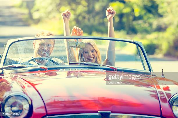 Front view of couple driving in a convertible car.