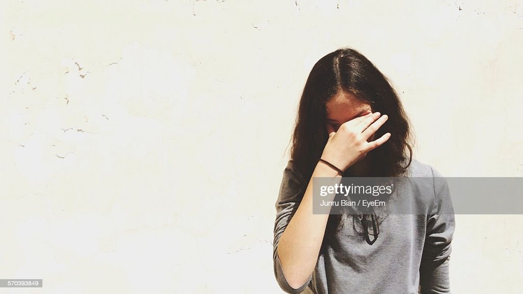 Front View Of Displeased Young Woman Against White Wall : Stock Photo