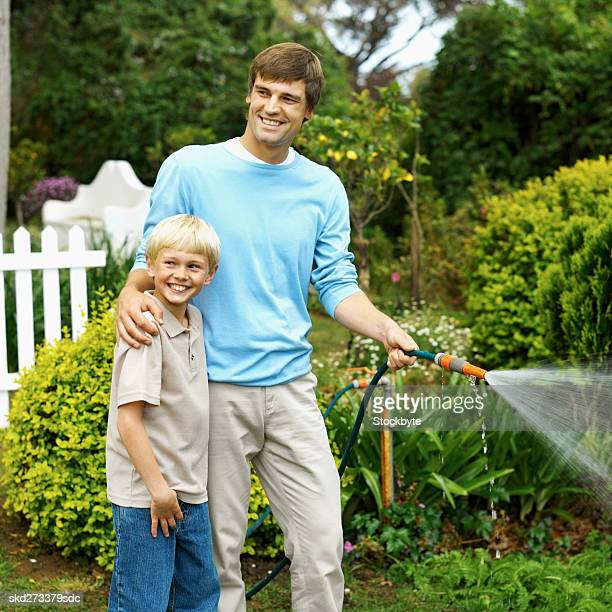 Front view of father sprinkling garden with water hose and arm around son (10-11)