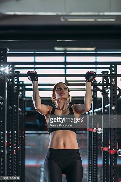 Front view of female athlete doing chin-ups at gym