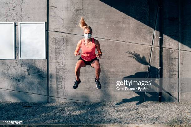 front view of fit and healthy caucasian woman with protective mask doing jumping squat - face guard sport stock pictures, royalty-free photos & images